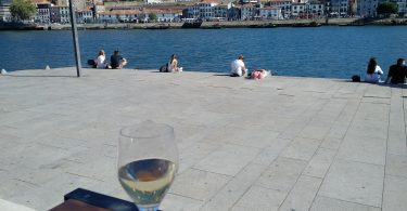 White wine glass on table in front of Porto's river with view to the other side