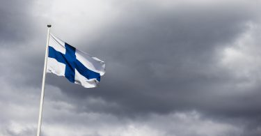 Finnish flag in front of dark clouds