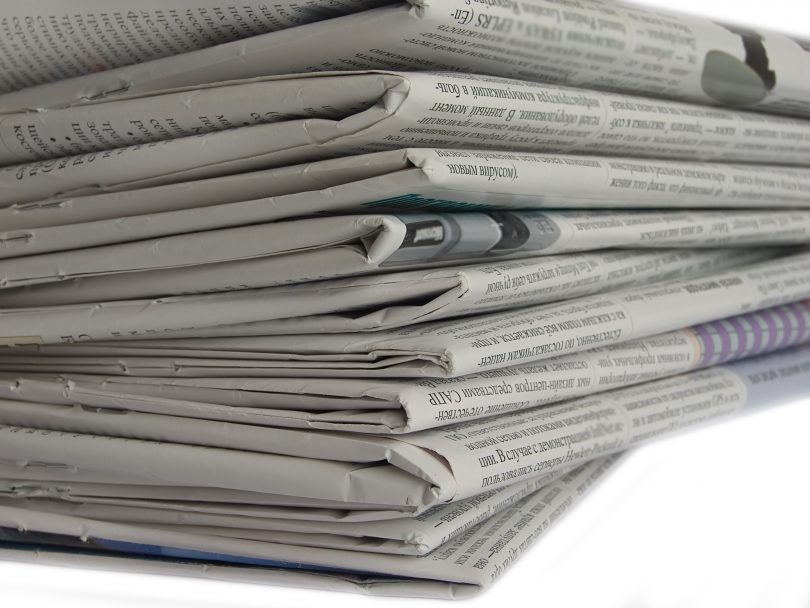 Foreign newspapers stacked up high. No newspaper's name is visible.