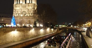 Notre Dame at night with boat on Seine river to the right