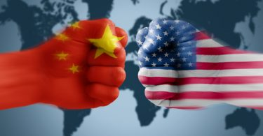Chinese and US fist confronting each other in front of world map