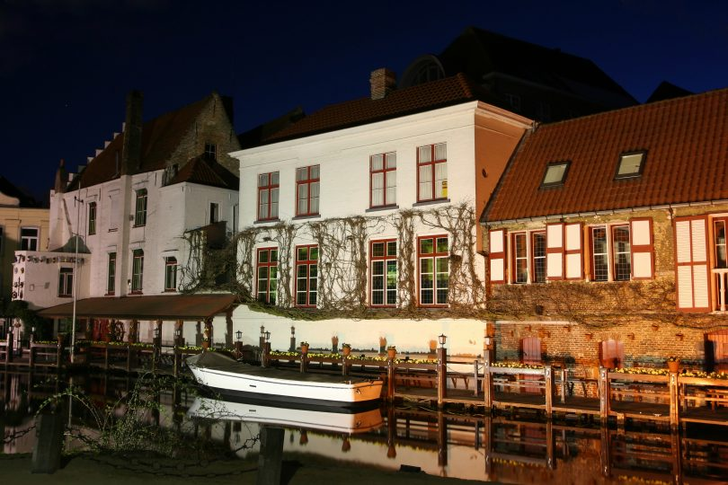 Bruges (Belgium) by night. A small boat near a row of old houses